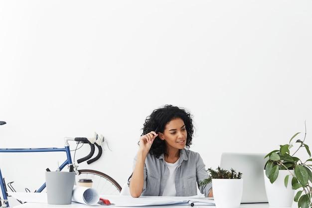 ビデオブログをオンラインで見ているカジュアルな服装の現代アフロアメリカン女子学生エンジニア
