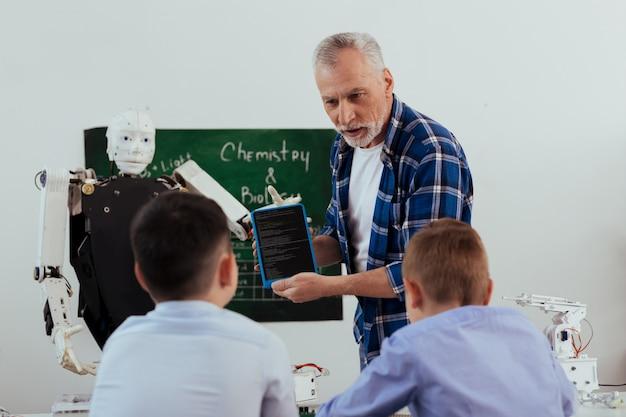Современный век. хороший пожилой учитель держит планшет во время разговора со своими учениками