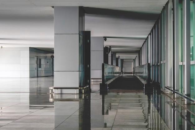 아무도 없는 현대적인 공항 홀 인테리어. 사람이 없는 텅 빈 공항 건물. 바닥에 직선 에스컬레이터입니다.