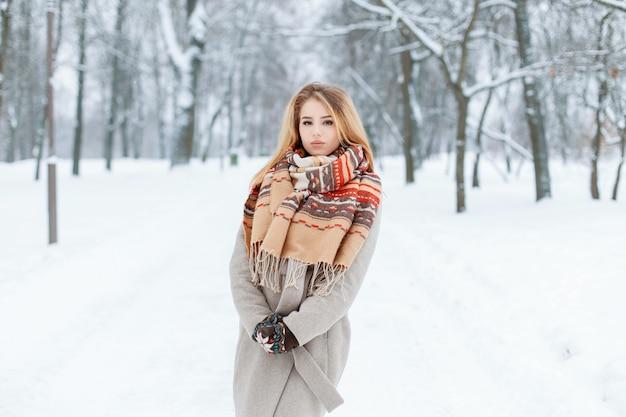 겨울 숲에서 야외에서 걷고 유행 겨울 빈티지 겉옷에 현대 놀라운 젊은 여자. 매력적인 소녀는 멋진 휴가를 보냅니다.