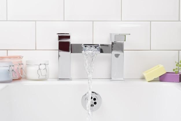 욕실에 세라믹 욕조가있는 현대적이고 새로운 스틸 수도꼭지