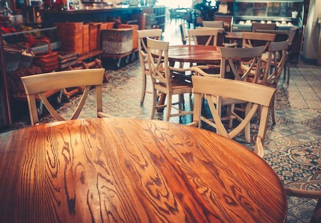 木製の古典的な家具と木製の床の丸いテーブルと椅子を備えたモダンでシンプルなカフェのインテリア
