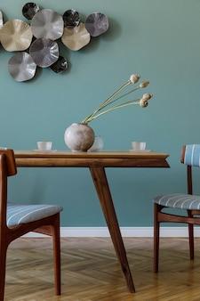 魅力的な木製のテーブル、エレガントな椅子、デザインの装飾が施されたモダンでスタイリッシュなダイニングルームのインテリア。レンプレート。室内装飾。緑の背景の壁。