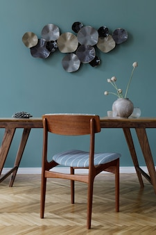 魅力的な木製のテーブル、エレガントな椅子、木製の寄木細工の床、デザインの装飾が施されたモダンでスタイリッシュなダイニングルームのインテリア。緑の背景の壁。レンプレート。室内装飾。