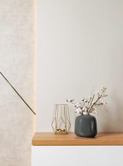 꽃병에 목화 가지와 금 장식 탁상 조각이있는 현대적이고 세련된 거실 인테리어 디자인. 가정 장식.