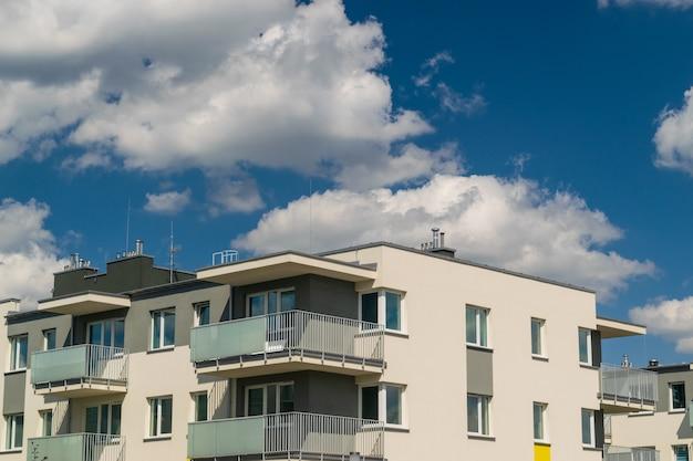 青空の背景にモダンなアパートの建物