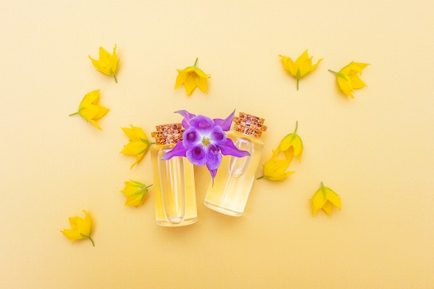 Modern apothecary. essential oil among flowers and petals. image in yellow and purple tones.