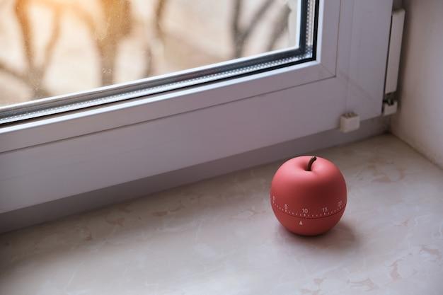 따뜻한 일출 조명이있는 창문 옆에 현대적인 사과 모양의 타이머