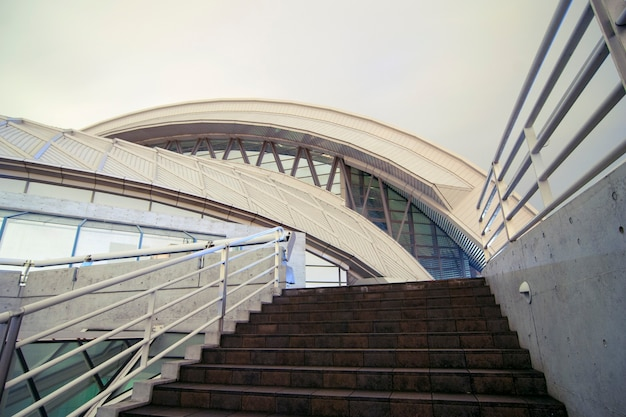 Modern architecture fragment with concrete stairs going to futuristic dome structure
