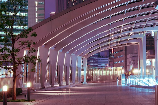 Modern architecture outdoor pathway under arc glass roof in the night
