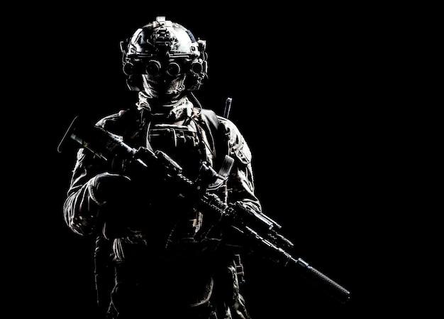 현대 육군 특수 부대 장비 군인, 테러 방지 분대 전사, 엘리트 용병 무장 돌격 소총, 헬멧에 야간 투시경을 쓰고 어둠 속에 서 있는, 스튜디오 초상화, 카피스페이스