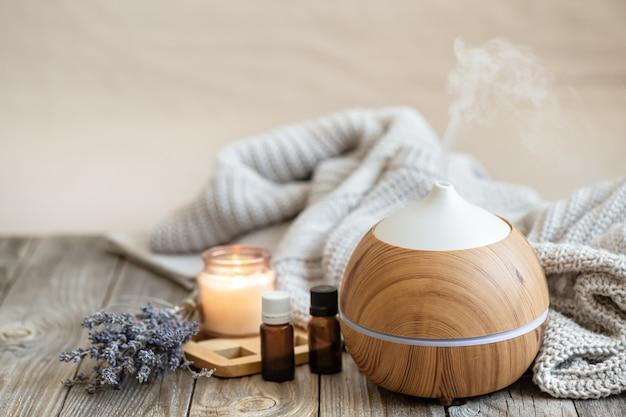 Современный диффузор ароматического масла на деревянной поверхности с вязанным элементом, свечой и маслом лаванды на размытом фоне.