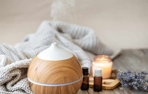 Modern aroma oil diffuser on wood surface with knitted element, candle and lavender oil