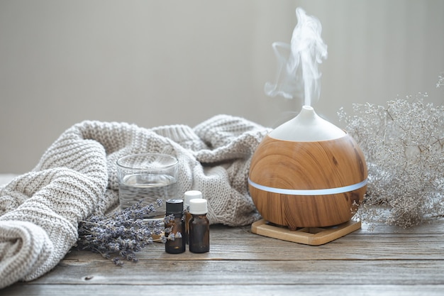 Modern aroma oil diffuser on wood surface with knitted element, water and oils in jars.