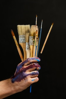 現代アートと創造性。ペイントツールと消耗品。暗い背景の上の男性の手で絵筆の束のクローズアップ。