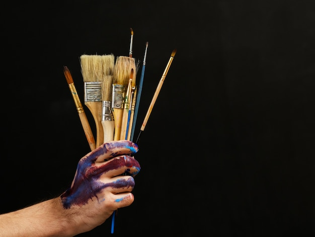 Modern art. painter essential tools. closeup of bunch of paintbrushes in male hand over dark background.