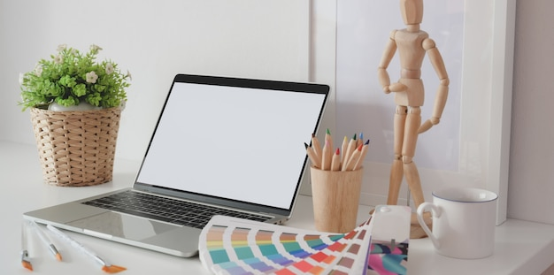 Modern artist creative studio with blank screen laptop computer, colour swatches and office supplies