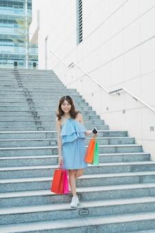 階下に行って買い物袋を持っている現代のアジアの女の子