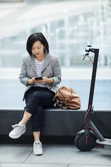 Современная азиатская женщина отдыхает в городской местности