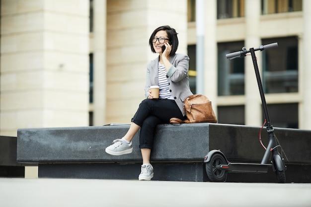 Современная азиатская женщина говорит по смартфон на открытом воздухе