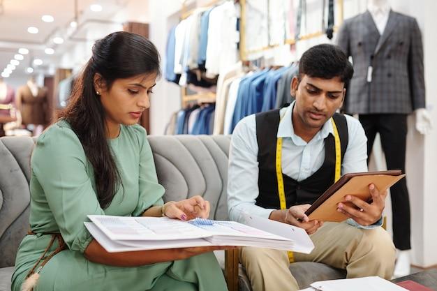 Современные владельцы ателье просматривают каталог с новыми образцами тканей и обсуждают, какие ткани и расходные материалы им необходимо заказать.