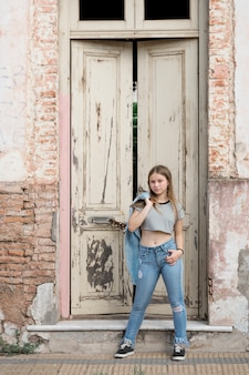 Modern attractive teenage girl posing near weathered door