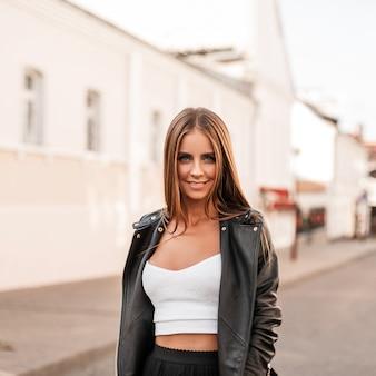 세련 된 검은 가죽 자 켓에 우아한 흰색 셔츠에 현대 매력적인 젊은 여성 패션 모델 야외에서 가을 날에 밝은 햇살을 즐깁니다. 꽤 즐거운 소녀는 도시를 걷는다.