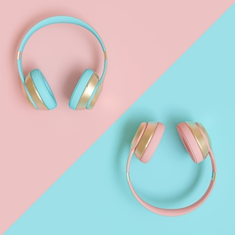 Modern audio headphones in gold, pink and blue on a flat lay bicolor paper