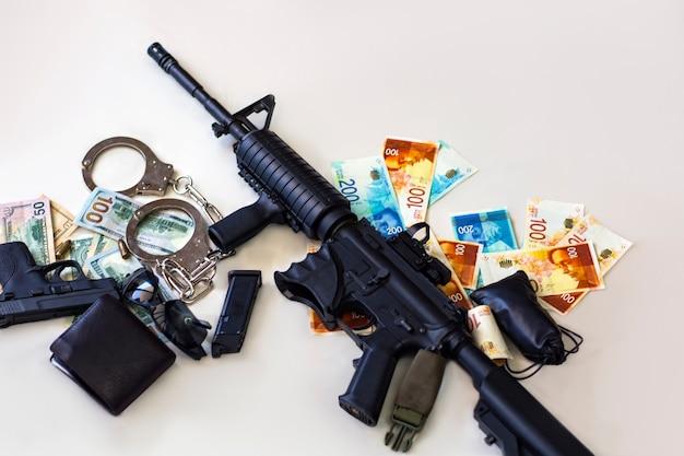 현대식 자동 소총, 권총, 총알 및 총알 9mm 탄약, 이스라엘 새 셰켈의 수갑, 미국 달러 지폐. 형사 돈과 처벌, 복사 공간. 금융 범죄 배너