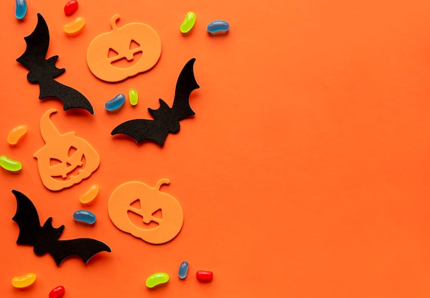 Modern background with bats  pumpkins candies on a orange background