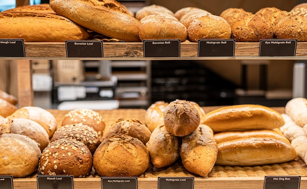 Modern bakery shop with assortment of bread on shelf.