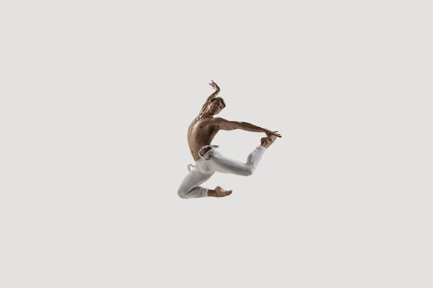 현대 발레 댄서입니다. 현대미술발레. 젊은 유연한 운동 남자... 스튜디오 촬영에 격리 된 흰색 배경. 부정적인 공간.