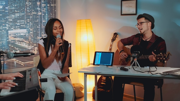 마이크에 노래 기타와 혼혈 소녀를 연주 홈 스튜디오 젊은 남자에서 리허설 현대 밴드