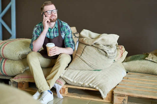 コーヒーとバッグの上に座ってモダンなバリスタ