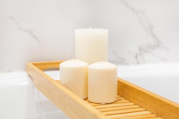 木製のテーブルとキャンドルを備えたモダンなバスルーム。白い大理石の背景の壁の側面図