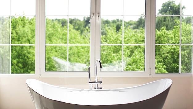 Современная ванная комната в светлом интерьере с большим окном и солнечным светом