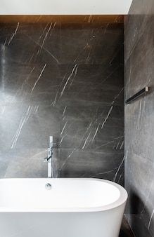 Интерьер современной ванной комнаты с ванной и коричневой стеной из натурального мрамора / дизайн интерьера / копия пространства