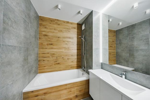 大きなスタイリッシュな鏡が付いたモダンなバスルームのインテリア。アパートの要素のインテリア。