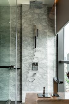 ステンレスシャワーセットと白い天然大理石の壁/インテリアデザイン/コピースペース付きのモダンなバスルームのインテリア