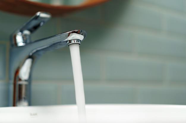 Интерьер современной ванной комнаты с белой чистой керамической раковиной
