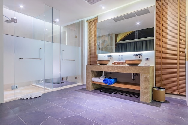 Modern bathroom in luxury apartment with glass walk in shower with grey tile surround