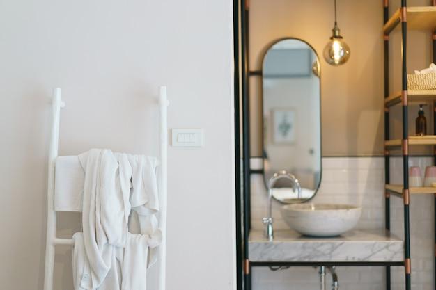 Современная ванная комната, зеркало со светящимися лампами и раковина, вешалка для полотенец на лестнице.