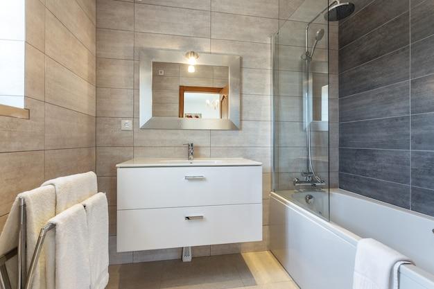 Современная ванная комната с душевой кабиной и умывальником для гигиены.
