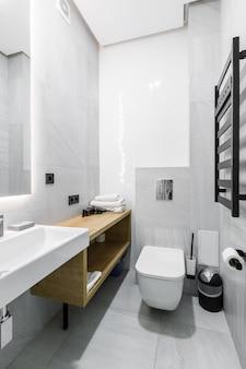 Современная ванная комната с душевой кабиной в небольшой квартире с белой мраморной плиткой