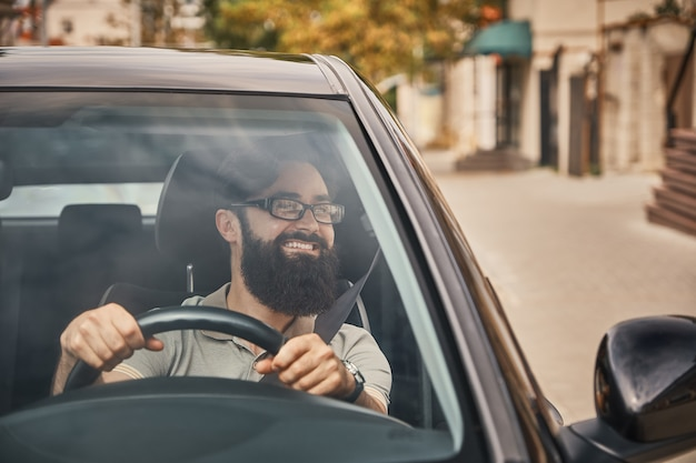 A modern bearded man driving a car