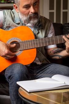 オンラインでギターのレッスンを受けている現代のひげを生やした男。オンライン学習の概念。
