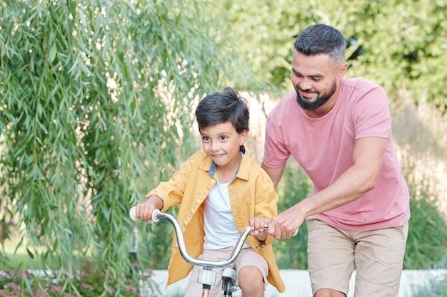 夏の日に裏庭で自転車に乗るように彼の陽気な幼い息子を教えている現代のひげを生やした男