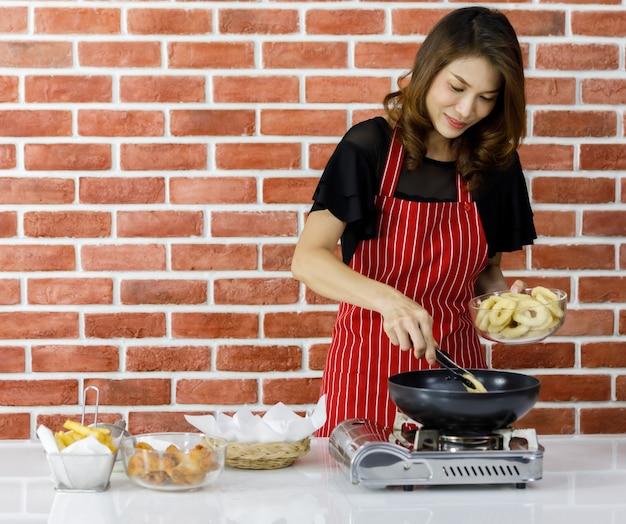 ガラスのボウルから黒い鍋にオニオンリングを入れて、キッチンのレンガの壁の近くのテーブルで揚げ物を調理するライフスタイルを楽しんでいるように笑っている赤い縞模様のエプロンのモダンな美しいアジアの主婦