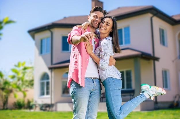 Современная красивая возбужденная молодая влюбленная пара стоит перед новым большим домом с ключами в руках и обнимается, празднуя эту покупку