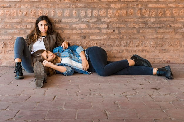 Modern beautiful girl lying on her female friends lap at outdoors